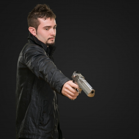 Portrait Of A Man Holding Gun against a black background Stock Photo - 16672339
