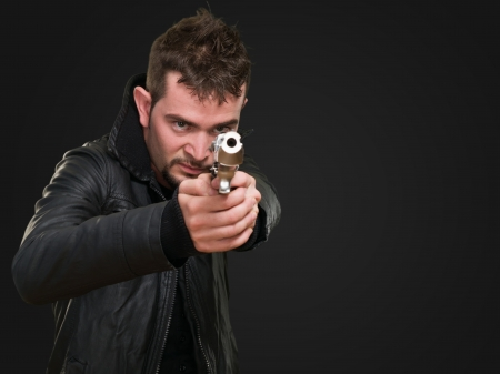 young man pointing with gun against a black background Stock Photo - 16671729