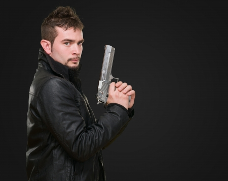 serious man holding a gun against a black background Stock Photo - 16672405