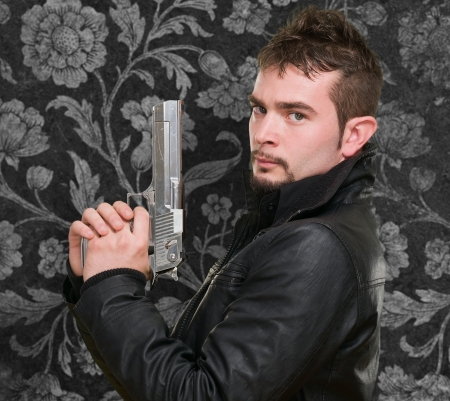 serious man holding a gun against a vintage background photo