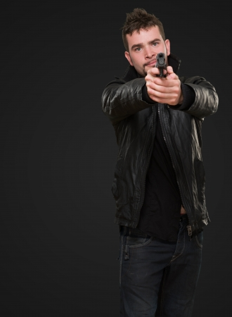 portrait of a man pointing with a gun against a black background Stock Photo - 16672390