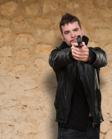 portrait of a man pointing with a gun against an old stone wall photo