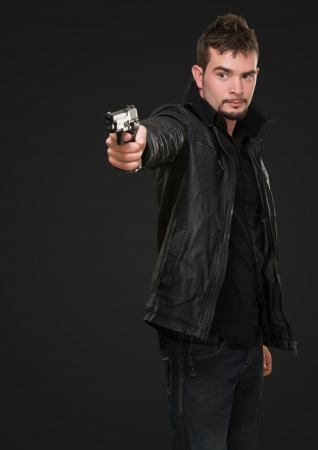 handsome man pointing with gun against a black background photo