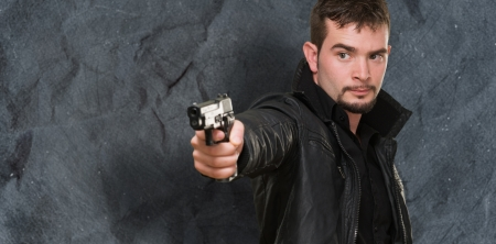handsome man pointing with gun against a grunge background Stock Photo - 16672362