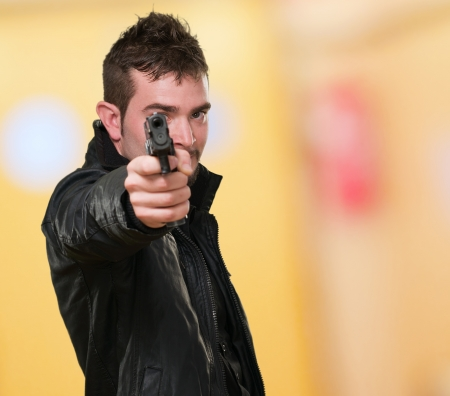 gun room: man with leather jacket pointing with gun against an abstract background Stock Photo