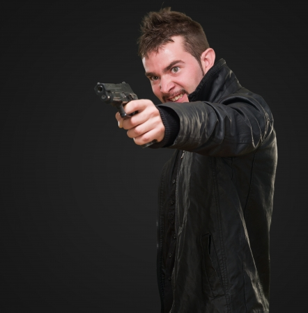 angry man pointing with gun against a black background photo