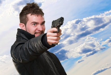 angry man pointing with gun against a cloudy sky background photo