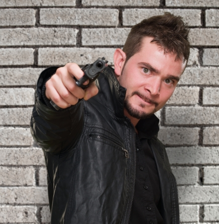 mad man pointing with gun against a brick wall Stock Photo - 16672374