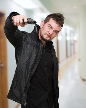 furious man pointing with a gun, indoor photo