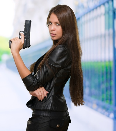 aggressive people: Portrait Of A Woman Holding Gun against a street background Stock Photo