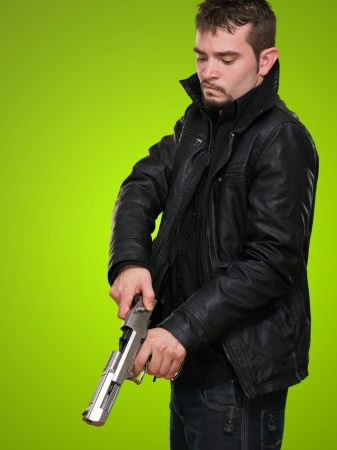 Portrait Of A Man Loading Gun against a green background Stock Photo - 16672465