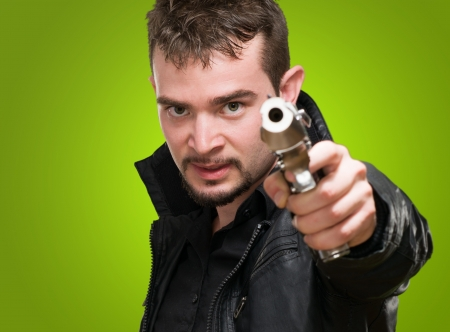 Portrait Of A Man Holding Gun against a green background Stock Photo - 16671725