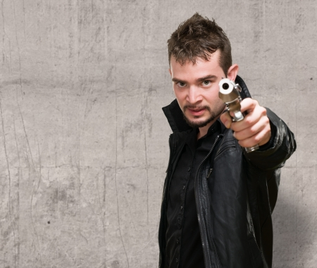 fusils: Portrait d'un homme tenant le pistolet contre un fond grunge