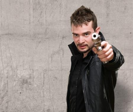 pistole: Ritratto Di Un Uomo azienda pistola su uno sfondo grunge Archivio Fotografico