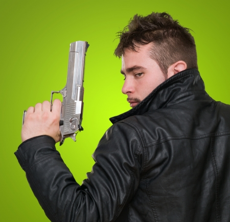 Portrait Of A Man Holding Gun against a green background photo