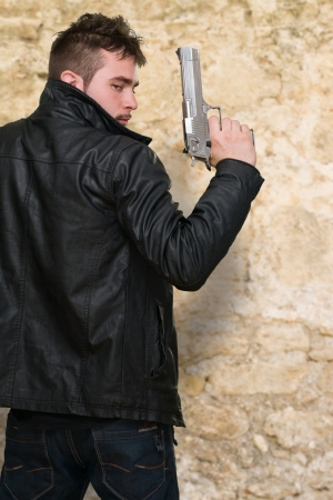 man holding gun: Portrait Of A Man Holding Gun against a stone background Stock Photo