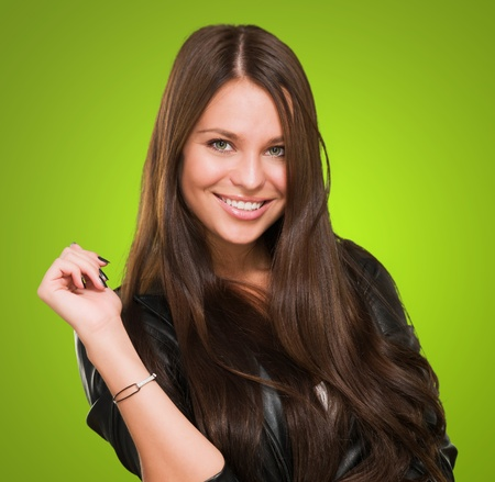 young happy woman posing against a green background photo