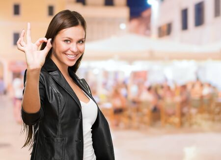 good looks: Portrait Of Cheerful Young Woman Gesturing Okay Sign, outdoor