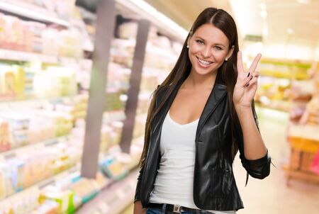 victory stand: Young Woman Giving Victory Sign at a supermarket