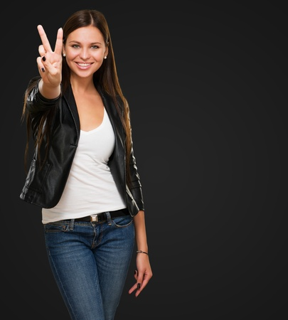 Beautiful Woman Giving Victory Sign against a black background Standard-Bild