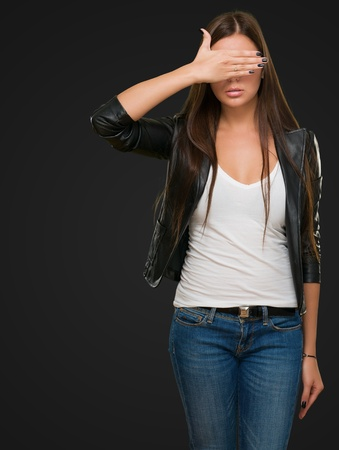 obscured face: Young Woman Covering Her Eyes against a black background Stock Photo