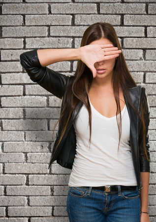 obscured face: Portrait of a Woman Covering Her Eyes against a brick wall Stock Photo