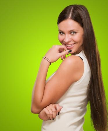 mani incrociate: Bella donna sorridente contro uno sfondo verde Archivio Fotografico