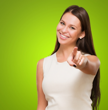 Portrait Of A Happy Young Woman Pointing At You against a green background Standard-Bild