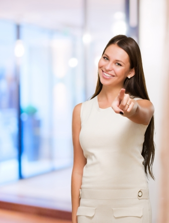 Portrait Of A Happy Young Woman Pointing At You against an abstract background