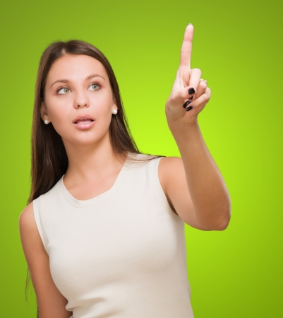 Portrait Of A Young Woman Pointing Up against a green background Standard-Bild