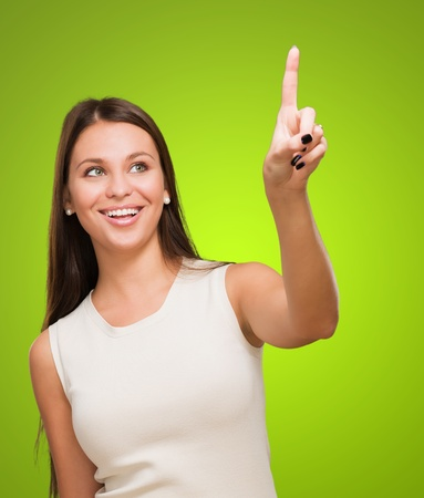 Portrait Of A Young Happy Woman Pointing Up against a green background photo