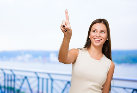 Portrait Of A Young Happy Woman Pointing Up, outdoor photo