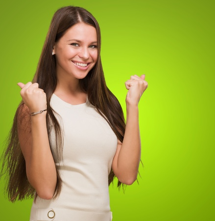 toothy smile: Happy woman doing a success gesture against a green background