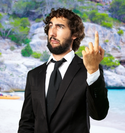 Portrait Of An Unhappy Businessman Pointing Up at the beach photo