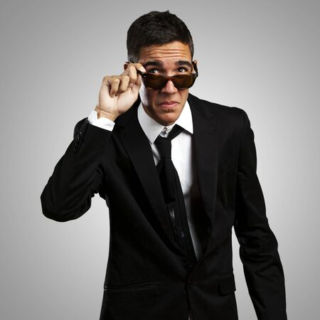 portrait of business man taking off the sunglasses against a grey background photo