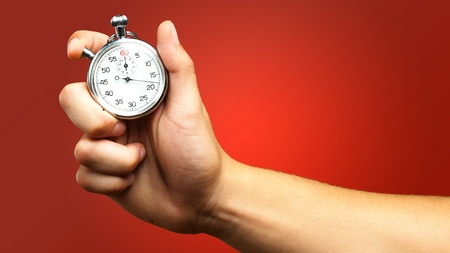 the timer: Close Up Of Hand Holding Stopwatch against a red background