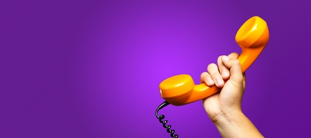 Close Up Of Hand Holding Telephone against a purple background Standard-Bild