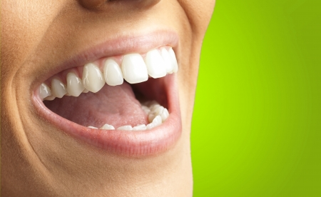 woman mouth open: Close Up Of Smiling Teeth against a green background