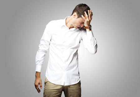 Angry young man doing frustration gesture over grey background Stock Photo - 17692106