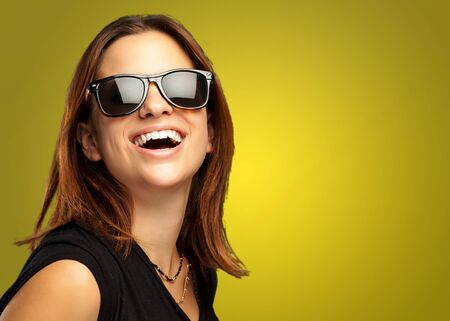 Portrait Of Happy Woman against a yellow background photo