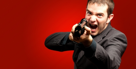 Angry Man Holding Gun against a red background photo