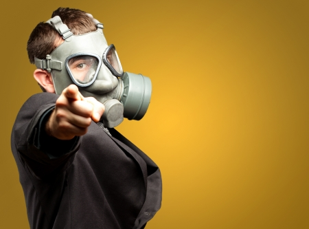 Businessman Pointing With Gas Mask against a yellow background