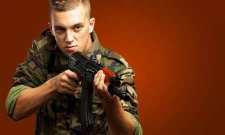 Portrait Of A Soldier Aiming With Gun against a red background Stock Photo - 17692414
