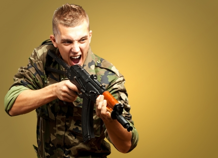 Portrait of an angry soldier aiming against a yellow background Stock Photo - 17692417