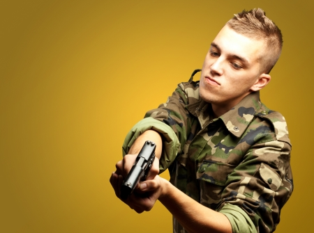 armed: portrait of a serious soldier aiming against an orange background