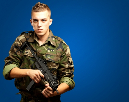 handsome soldier holding gun against a blue background Stock Photo - 17692413