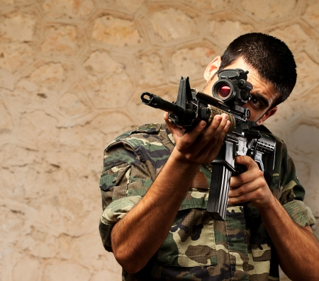 assault rifle: Soldier Gunman Aiming His Target against a brown rock Background