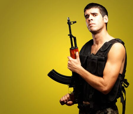 Portrait Of Soldier Holding Gun against a yellow background photo