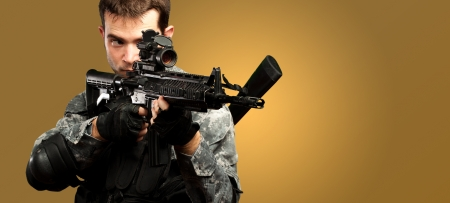 Portrait Of A Soldier Holding Gun against an orange background Stock Photo - 17692671