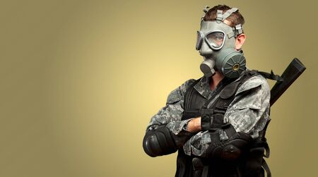 Portrait Of A Soldier With Gas Mask against a yellow background photo